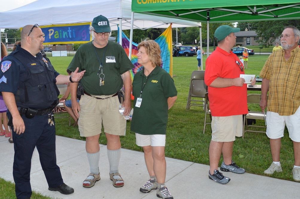 A Villa Park Police Officer talks with members of the Community Emergency Response Team (CERT) at a National Night Out event at the Iowa Community Center, Aug. 2.